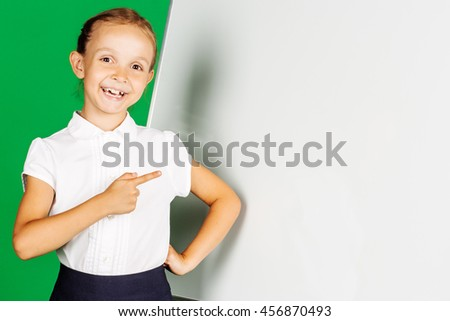 portrait of school girl in a school uniform near whiteboard with . Learning, idea and school concept. Image on green background. - stock photo