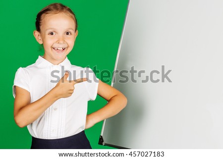 portrait of school girl in a school uniform near whiteboard with pointing at the whiteboard. Learning, idea and school concept. Image on green background. - stock photo