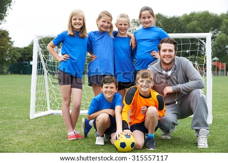 Portrait Of School Soccer Team With Coach - stock photo