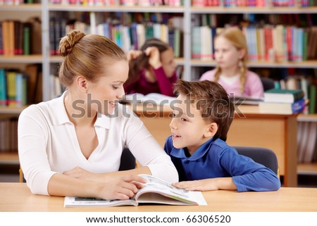 Portrait of schoolboy and teacher reading and discussing interesting book - stock photo