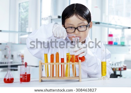 Portrait of schoolboy doing chemistry experiment while wearing coat in the laboratory - stock photo