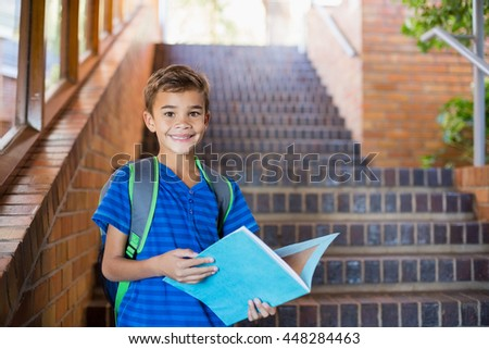 Portrait of schoolboy holding a book on staircase at school - stock photo