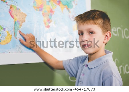 Portrait of schoolboy pointing at map in classroom at school - stock photo