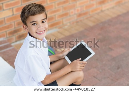 Portrait of schoolboy sitting in corridor and using digital tablet at school - stock photo