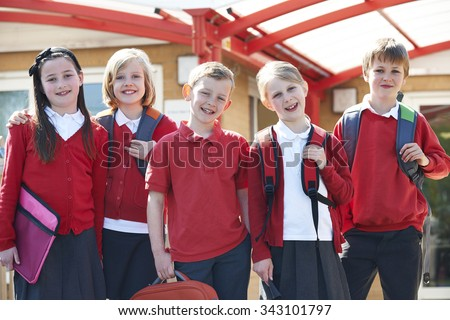 Portrait Of Schoolchildren Outside Classroom Carrying Bags - stock photo