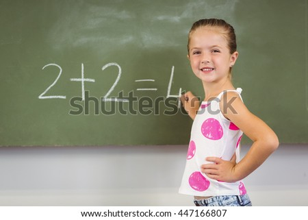 Portrait of schoolgirl doing mathematics on chalkboard in classroom at school - stock photo