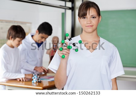 Portrait of schoolgirl holding molecular structure with classmates in background - stock photo