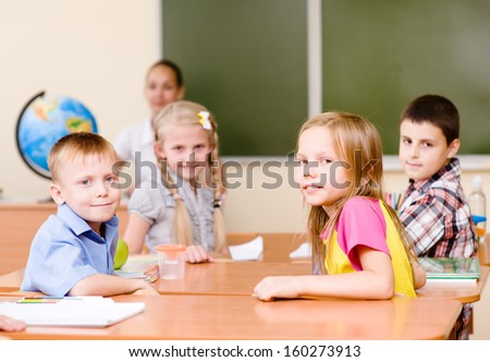 Portrait of schoolkids at workplace with teacher on background - stock photo