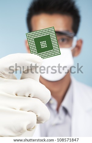 Portrait of scientist showing a microchip computer. shot in studio - stock photo