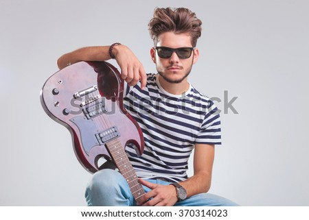 portrait of seated young man with guitar in hand resting while posing in studio background - stock photo