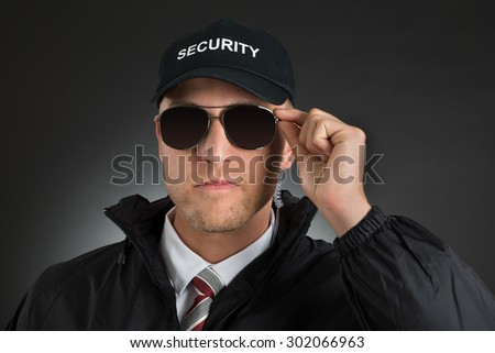 Portrait Of Security Guard Wearing Sun Glasses Over Black Background - stock photo
