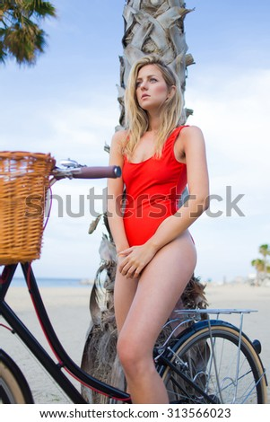 Portrait of seductive hipster woman in bikini sitting on classic bicycle resting after ride, gorgeous young female dressed in red sexy swimwear with a perfect figure posing for camera on the beach  - stock photo