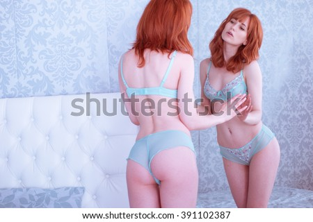 Portrait of seductive young ginger woman looking into the mirror - stock photo