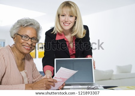 Portrait of senior African American woman being assisted by financial adviser for paperwork - stock photo