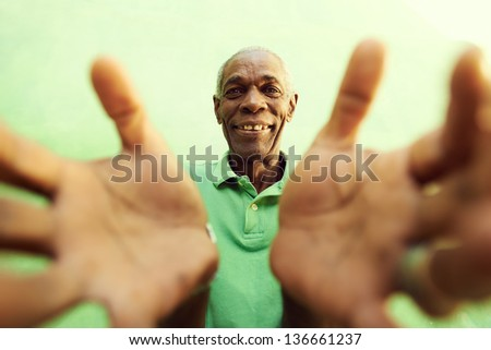 portrait of senior black man with hands and arms open pointing at camera. Green background - stock photo
