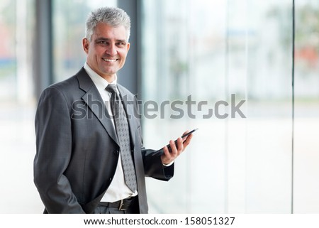 portrait of senior business executive using tablet pc - stock photo