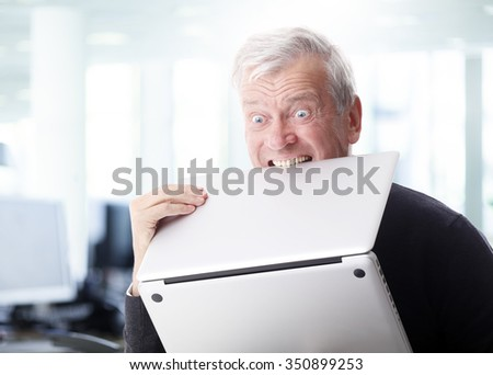 Portrait of senior businessman holding laptop in hand while frustrated with his computer. 