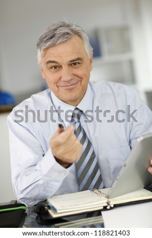 Portrait of senior businessman in office using tablet - stock photo