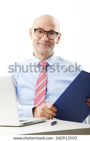 Portrait of senior businessman sitting at desk in front of laptop while holding file in his hand. Isolated on white background.  - stock photo