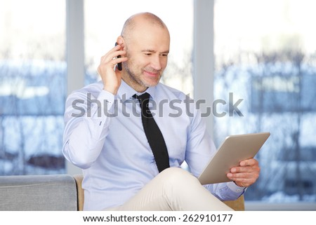 Portrait of senior businessman sitting at office while making call and holding digital tablet in his hand. Business people at work.  - stock photo