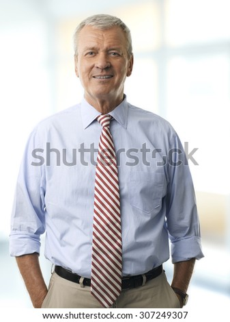 Portrait of senior businessman standing at office while looking at camera and smiling.  - stock photo