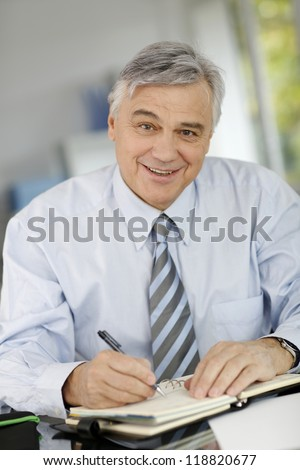 Portrait of senior businessman writing on agenda - stock photo