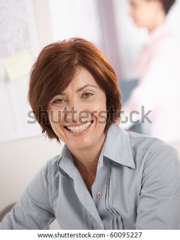 Portrait of senior businesswoman smiling at camera, coworker in background.? - stock photo