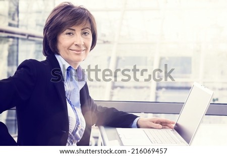 Portrait of senior businesswoman with laptop at office, Large copyspace. - stock photo