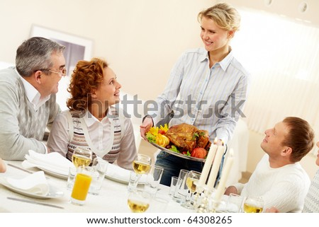 Portrait of senior couple and happy man pretty woman with roasted turkey going to put it on festive table - stock photo