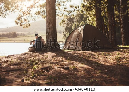 Portrait of senior couple camping by a lake. Man and woman sitting under a tree looking away a the lake on summer day. - stock photo