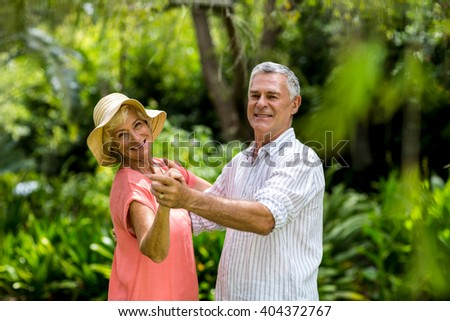 Portrait of senior couple dancing in yard - stock photo