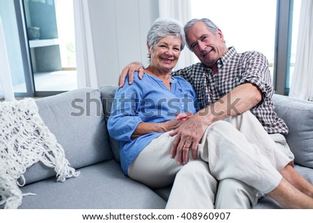 Portrait of senior couple embracing each other on sofa in living room - stock photo