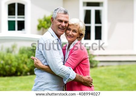 Portrait of senior couple embracing outside house at yard - stock photo