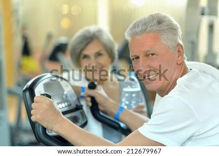 Portrait of senior Couple Exercising In gym - stock photo