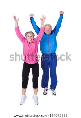 Portrait Of Senior Couple Jumping In Joy Over White Background - stock photo