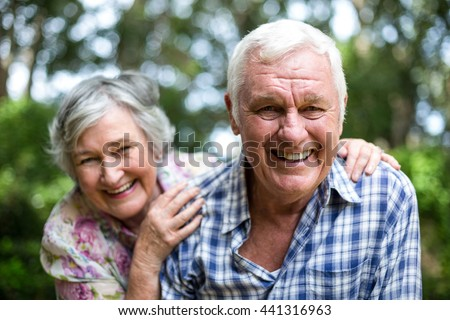 Portrait of senior couple laughing against trees in back yard - stock photo