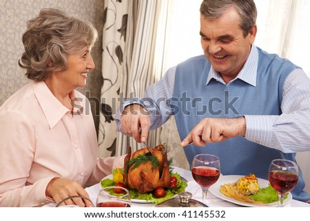 Portrait of senior couple sitting at Christmas table while happy man cutting roasted turkey - stock photo