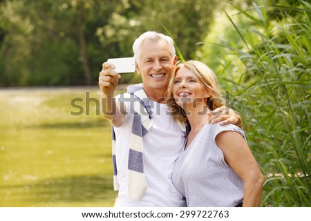Portrait of senior couple sitting at lakeside. Elderly man hugs her wife while take self portrait with mobile. - stock photo