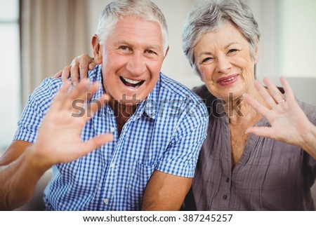 Portrait of senior couple sitting on sofa and smiling in living room - stock photo
