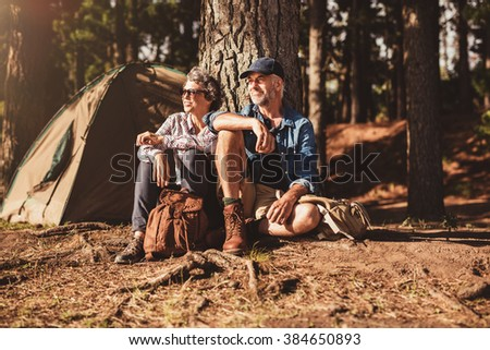 Portrait of senior couple sitting together under a tree in forest and looking at a view. Mature man and woman relaxing at their campsite. - stock photo