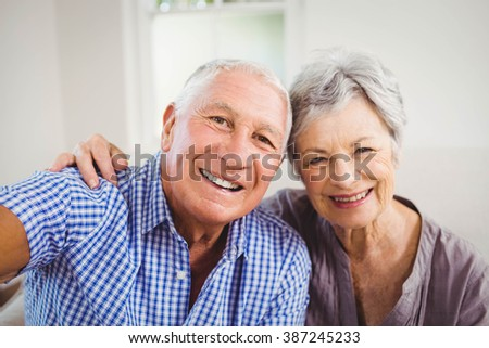 Portrait of senior couple smiling in living room - stock photo