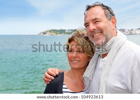 Portrait of senior couple standing by the sea - stock photo