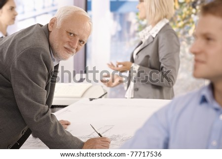 Portrait of senior designer at work, looking at camera, surrounded by young colleagues.? - stock photo