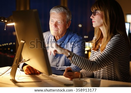 Portrait of senior director and financial professional woman sitting in front of computer and working at late night at office.  - stock photo