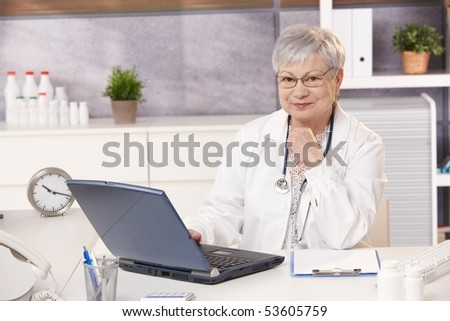 Portrait of senior doctor in office, sitting at desk, looking at camera, smiling. - stock photo