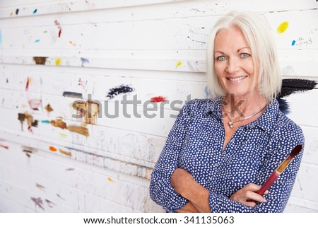 Portrait Of Senior Female Artist Against Paint Covered Wall - stock photo