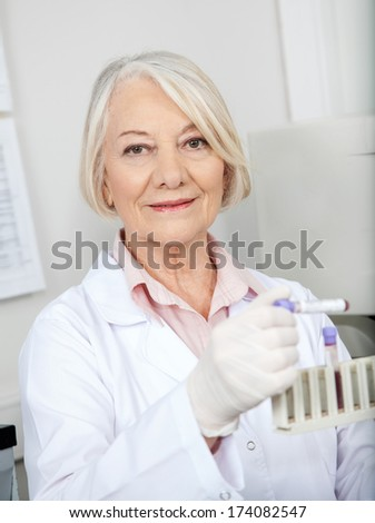 Portrait of senior female scientist analyzing blood sample in medical laboratory - stock photo