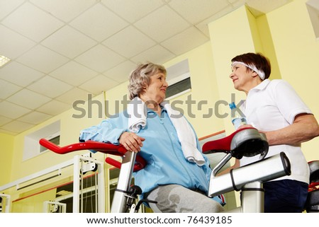 Portrait of senior females refreshing and chatting while sitting on facilities - stock photo