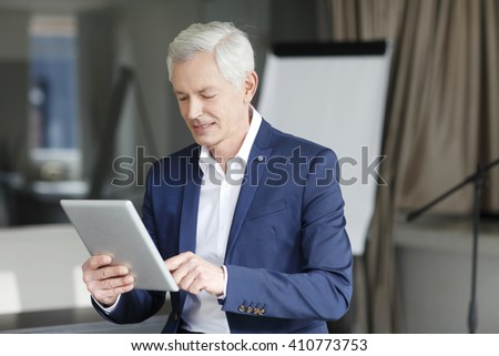 Portrait of senior financial director working on digital tablet while sitting at office after business meeting. - stock photo