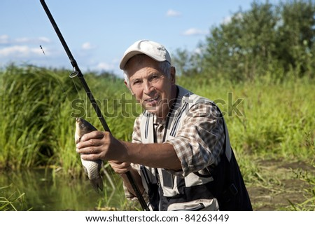 Portrait of senior fisherman with rod and fresh catch - stock photo